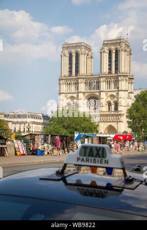 Paris, France - July 7, 2018: View of the Notre Dame de Paris on the island Cite in Paris against the background of the sign on the roof of a taxi Tax - Stock Photo