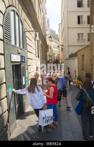 Paris, France - July 7, 2018: A narrow street in the Latin Quarter of Paris on the left bank of the Seine with many tourists walking and shopping - Stock Photo