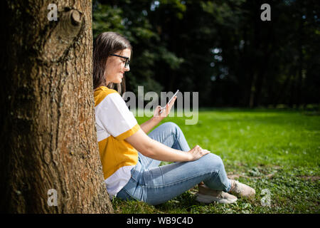 Student girl checking her smartphone resting against a tree in park - Stock Photo
