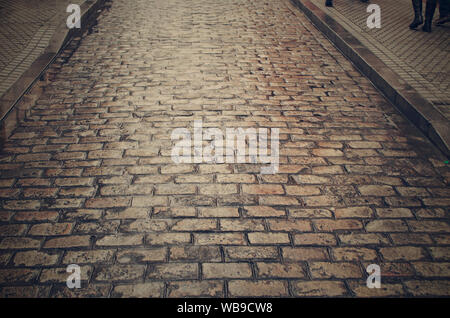 Closeup of a cobblestone street on a rainy day in Seville, Andalusia, Spain - Stock Photo