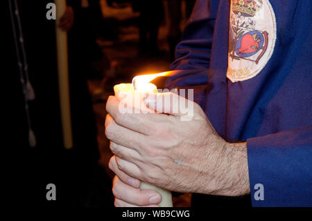 Closeup of the hands of a penitent nazarene holding his candle during a procession. Holy Week, Seville, Andalusia, Spain. Nocturnal procession of the - Stock Photo