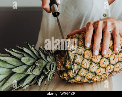 Blonde woman with green eyes in modern kitchen and about to prepare a pineapple. Stock Photo