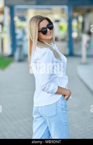 Pretty girl posing on street near office building - Stock Photo