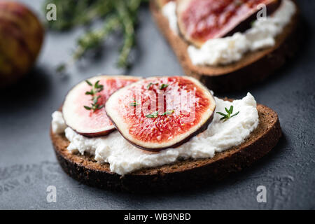 Rye bread toast with figs and ricotta cheese on black slate background, closeup view, selective focus. Healthy food - Stock Photo