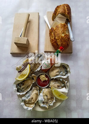 Raw oysters on the half shell. Appetizer at Seattle's Crab Pot restaurant. - Stock Photo
