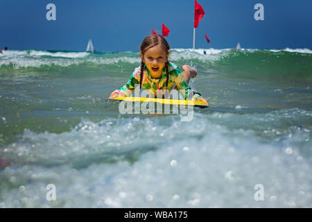 Happy baby girl - young surfer ride on surfboard with fun on sea waves. Active family lifestyle
