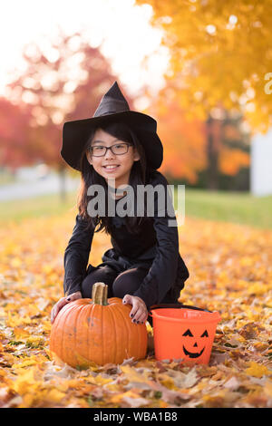 Portrait of little asian girl in witch costume - Stock Photo