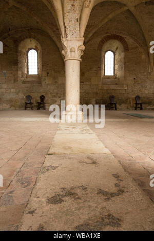 Interior space at the Abbey of San Galgano in Chiusdino, Italy. Stone floors and vaulted ceilings with old chairs in the distance. - Stock Photo