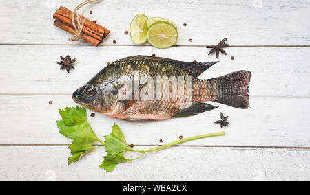 Tilapia fish freshwater and lemon lime herb spices vegetable for cooking food in the asian restaurant / Fresh raw tilapia on wooden background - Stock Photo