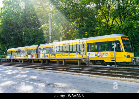 Stuttgart, Germany, August 16, 2019, Yellow train of ssb line u34 to vogelsang waiting at train station suedheimer platz square next to green forest t - Stock Photo