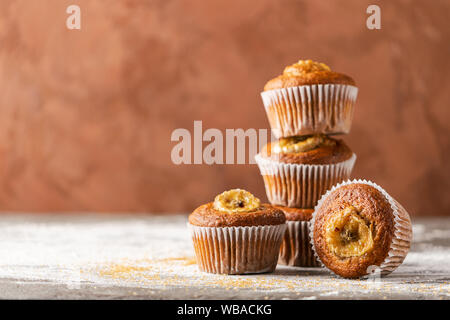 Homemade banana muffins in a stack on a brown background. Healthy vegan dessert. Close-up selective focus. Horizontal frame. Copy space - Stock Photo