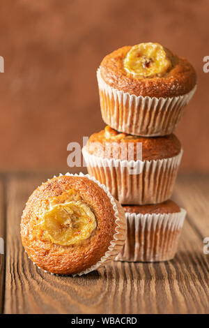 Homemade banana muffins in a stack on a brown background. Healthy vegan dessert. Close-up selective focus. Copy space. Vertical frame. - Stock Photo