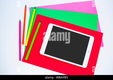 Colorful paper, neon pencils and tablet on white background with copyspace. Flat lay style. Back to school concept. - Stock Photo
