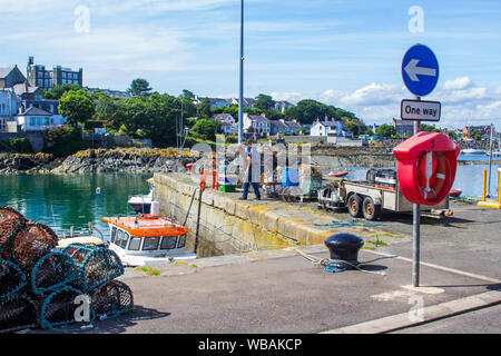 8 August 2019 A man working on the harbour quay side in the small fishing village of Ardglass in County down Northern Ireland on a hot summer day. - Stock Photo
