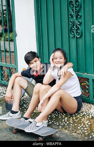 Smiling twin brother and sister sitting in the street with their skateboards and looking away - Stock Photo