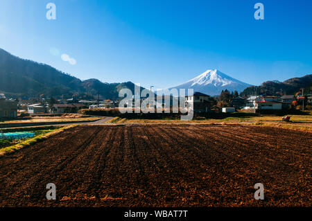Snow covered Mount Fuji and local town along train route from Tokyo to Kawaguchiko seen through train window with some mirror reflect on left side - Stock Photo