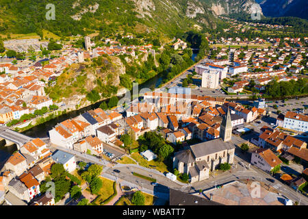Scenic aerial view of Tarascon-sur-Ariege overlooking ancient Sainte Quitterie Church and round castle tower on tophill on bank of Ariege river - Stock Photo