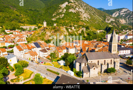 View from drone of small French town of Tarascon-sur-Ariege on banks of Ariege river in valley of Pyrenees on background of summer mountain landscape - Stock Photo