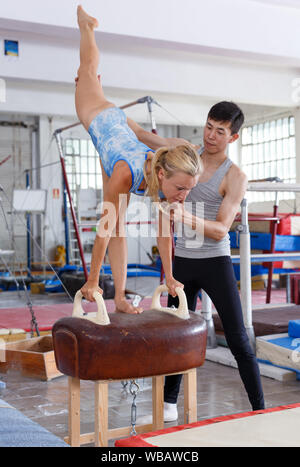 Fit man and woman doing acrobatic exercises on pommel horse in the gym securing each other - Stock Photo