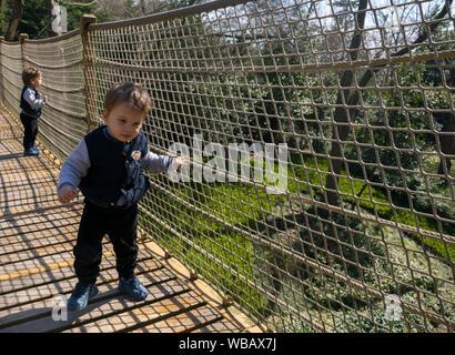 Child walking on the suspension bridge - Stock Photo