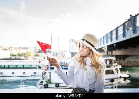 Attractive young beautiful girl waves Turkish flag over Galata Bridge and enjoys view of bosphorus in Istanbul,Turkey. Traveler concept. - Stock Photo