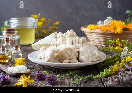 Shea butter with beeswax, medicinal plant and essential oils - ingredients for preparing a homemade skin cream. - Stock Photo
