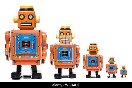 Vintage tin robot toy in different size scales isolated on a white background. - Stock Photo
