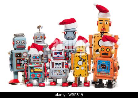 Vintage tin robot toys with xmas hats isolated on a white background. - Stock Photo
