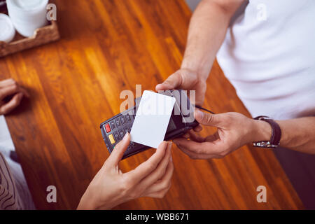 Top view of female hand holding credit card paying with wooden counter in background - Stock Photo