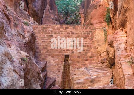 Dam in Siq canyon in Petra historical city of Nabatean Kingdom in Jordan. - Stock Photo