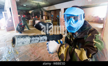 Portrait of blue team happy cheerful positive player who is aiming in opponents on paintball field. - Stock Photo