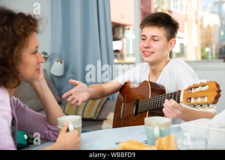 Positive teenage boy with mother enjoying time at home, having friendly conversation and playing guitar - Stock Photo