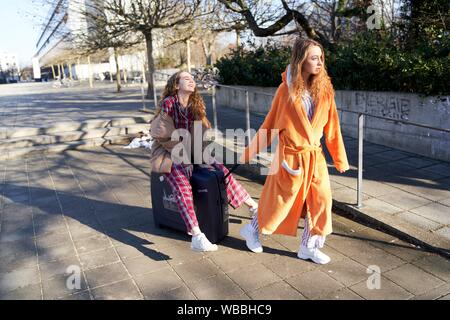 two young sleepy women in pyjama and bathrobe at university campus with trolley case - Stock Photo