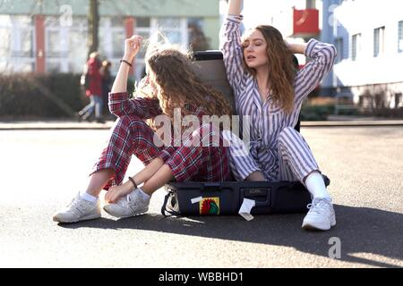 two young women in pyjamas sitting in trolley case at street - Stock Photo