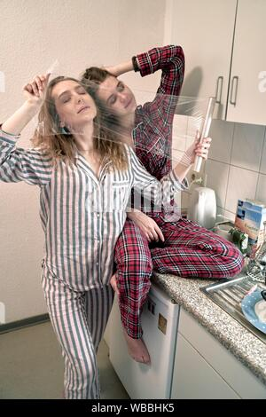two young women behind plastic foil in kitchen, wearing pyjamas