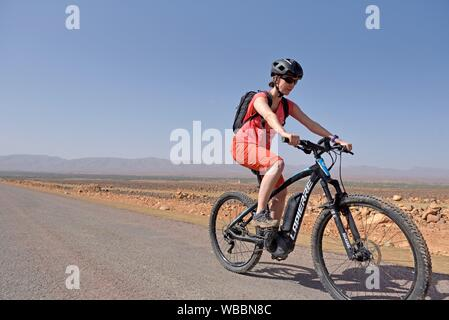 young woman mountain biking with electric assistance on a straight road through the reg, from Agdz to Zagora, Draa River valley, Province of Zagora, - Stock Photo