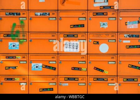 Amsterdam, Netherlands. Metal and organen colored mail boxes near the entrance to a student´s dormitory aimed at receiving old and diminishing - Stock Photo