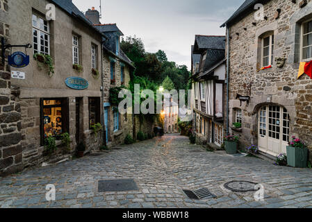Dinan, France - July 23, 2018: Old cobblestoned street with medieval houses  at dusk, French Brittany - Stock Photo