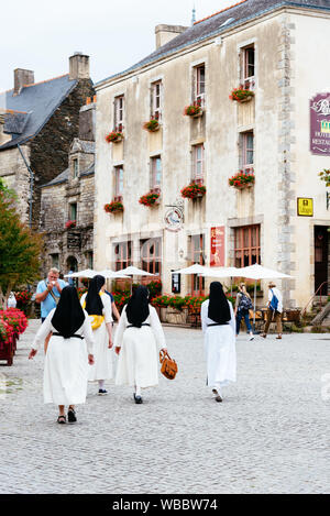 Rochefort-en-Terre , France - July 26, 2018: Nuns walking by the picturesque medieval village, one of the most beautiful towns in Brittany - Stock Photo