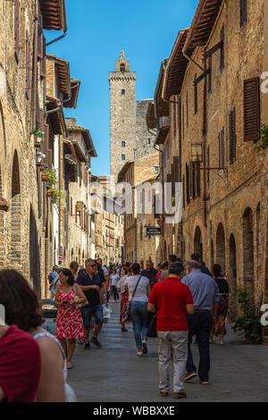 Tourists in San Giovanni street, San Gimignano - Stock Photo