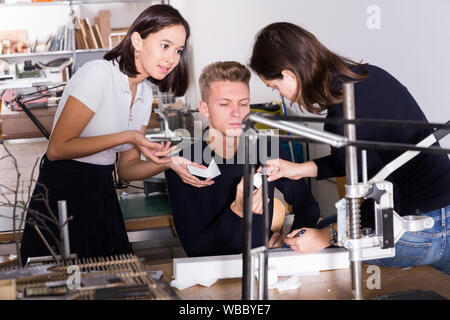 Students and teacher of architecture faculty discussing details of architectural model in university workshop - Stock Photo