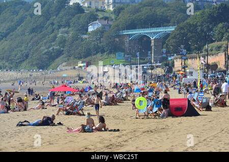 Scarborough, North Yorkshire, UK, 26th August 2019, Weather: Hot and sunny August bank holiday Monday morning and temperature records are expected to be broken across eastern England for the late summer holiday. People flock to the seafront and beach from miles around to have fun in the sun in this traditional English seaside town on the north east coast. Credit: Paul Biggins/Alamy Live News - Stock Photo