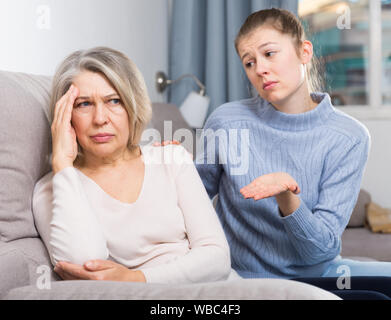 Portrait of offended senior woman turned away from her adult daughter - Stock Photo