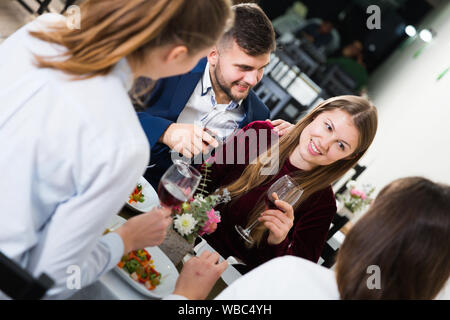 Friends are having dinner in the restaurante indoor. - Stock Photo