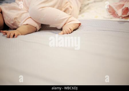 baby crawling and rolling around on the bed. soft and tenderness small baby feet laying on the soft bed sheets. growing up in a loving comfort family. - Stock Photo