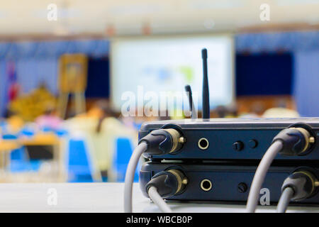 Close up Jack plug cables connected with old box of wireless microphone in conference meeting room seminar business blur. - Stock Photo