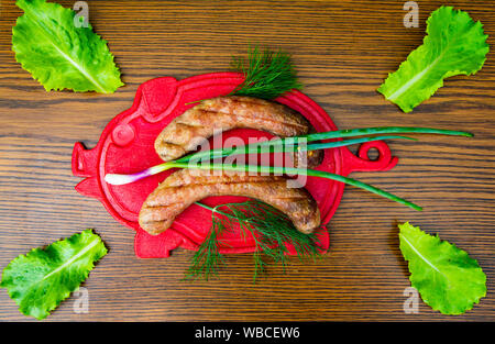 Bavarian sausages on a cutting board with vegetables - cucumber, tomato, green salad. View from above. Place for text. - Stock Photo