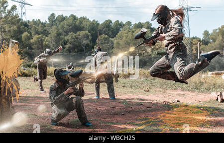 Dynamic paintball battle. Portrait female player jumping and aiming marker on member of opposing team - Stock Photo
