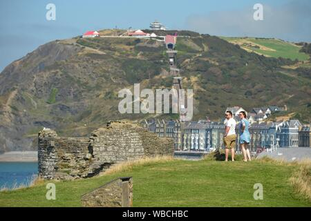 Aberystwyth, UK. 26 August 2019. UK Weather: People enjoying another day of hot sunshine and clear blue skies at the seaside in Aberystwyth on the August Bank Holiday Monday.