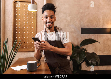 Happy young man barista wearing apron standing at the coffee shop, using mobile phone - Stock Photo